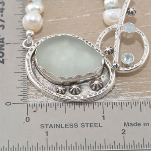 Sea glass pendant in a handcrafted sterling silver setting accented with a pale topaz and a milky aquamarine on a hand knotted necklace of cultured pearls and amazonite chips. (N517)
