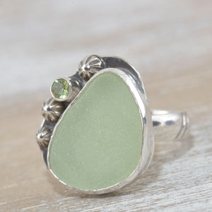 Sea glass ring with pale green sea glass accented with  a sparkly peridot in sterling silver. (R528)