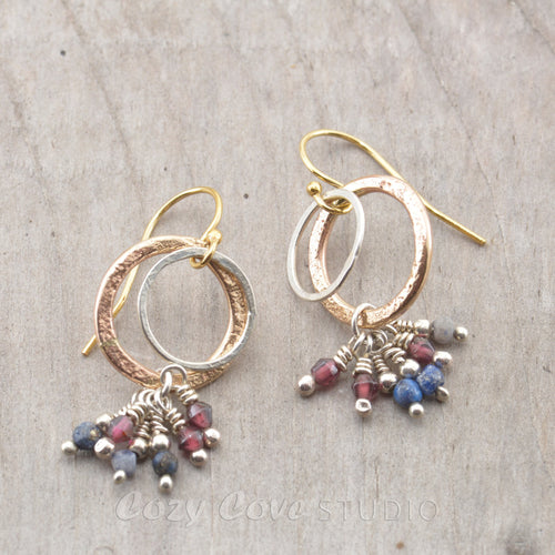 Mixed metal double hoops of 14K gold fill and sterling silver with dangles of lapis lazuli and garnet beads.