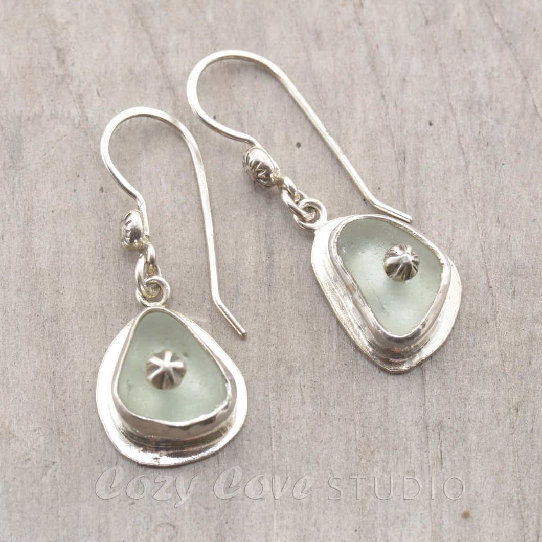 Sea glass earrings in pale blue accented with sterling silver studs.