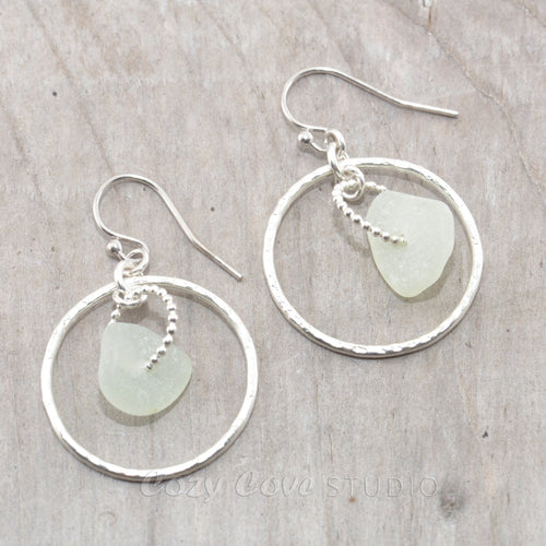 Pale green sea glass earrings encircled by textured hoops of sterling silver.