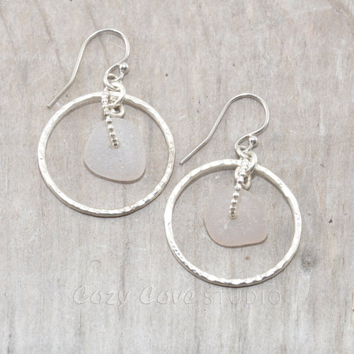 Pale lavender sea glass earrings encircled by textured hoops of sterling silver.
