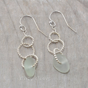 Sea glass dangle earrings on circle of sterling silver beaded wire.