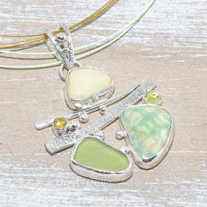 Sea glass and vitreous enamel pendant necklace in a hand crafted setting of sterling silver accented with semi-precious gemstones. (N619)