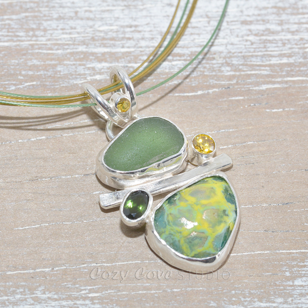 Sea glass and vitreous enamel pendant necklace in shades of yellow and green in a handcrafted setting of sterling silver accented with semi-precious gemstones. (N621)