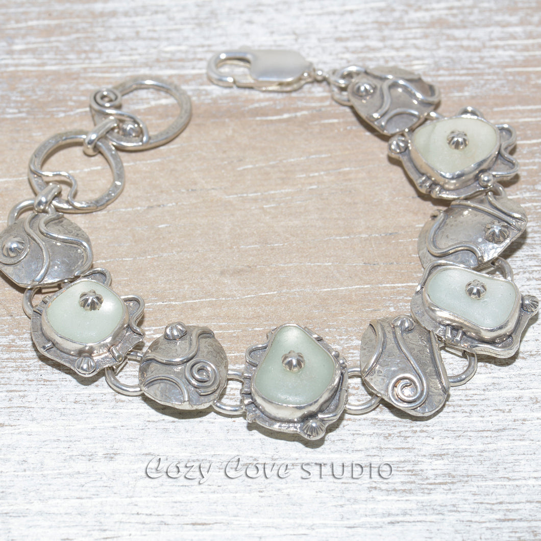 Sea glass bracelet accented with sterling studs with hand crafted links of sterling silver. (B634)