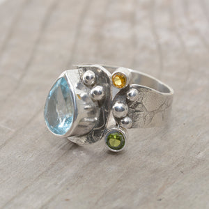 Artisan ring with a sparkly pear shaped blue topaz in a hand crafted setting of tarnish resistant sterling silver. (R681)