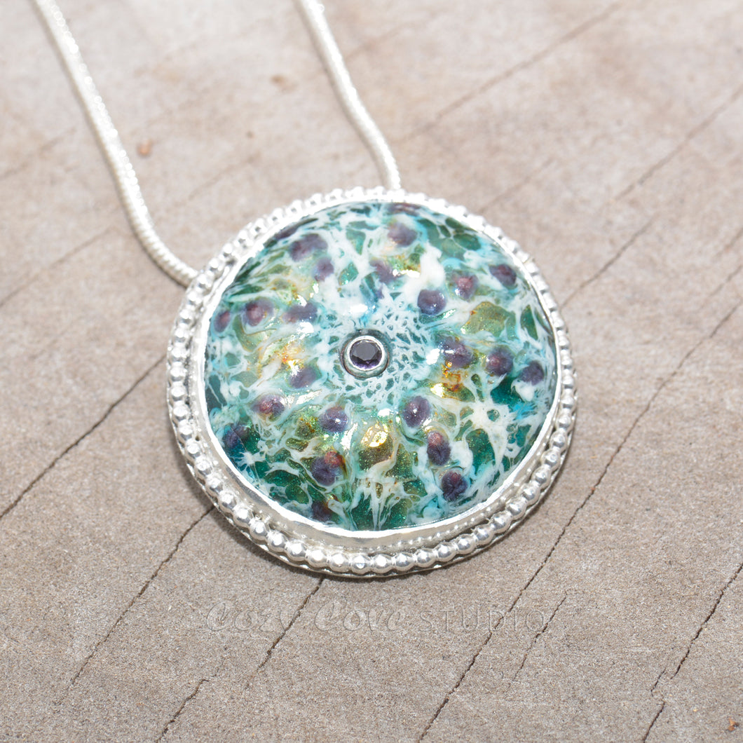 Enamel sea urchin pendant necklace accented with a gemstone in a hand crafted sterling silver setting. (N685)