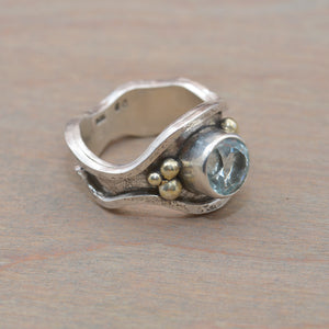 Aquamarine ring in a hand crafted sculptural setting of sterling silver accented with 24K gold. (R704)