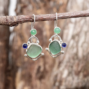 Teal sea glass dangle earrings accented with a sapphire cabochon and citrine cabochon in settings of sterling silver. (E718)