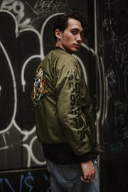 Olive nylon bomber jacket, influenced by the Chinese Zodiac Monkey with zipper on the left sleeve and the monkey birth year on the right sleeve.  Has the monkey characteristic on the left chest with orange and black design inside the jacket. Back of the Jacket is an embroidery of the Monkey with inside pocket on the left side.