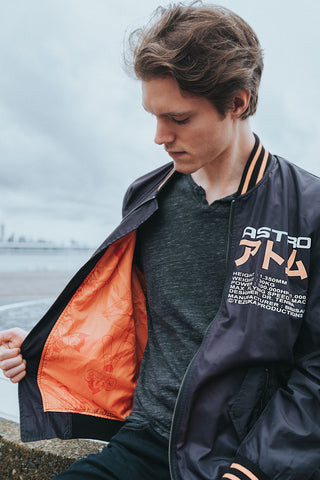 Black Nylon Astroboy Bomber jacket in black and orange. Has a zipper with an orange tag on the left sleeve with Astroboy written on one side and Bibisama on the other. Has Astroboy x Bibisama patch on the right sleeve. On the left chest, Astroboy is written on top with information on manufacturer and designer.