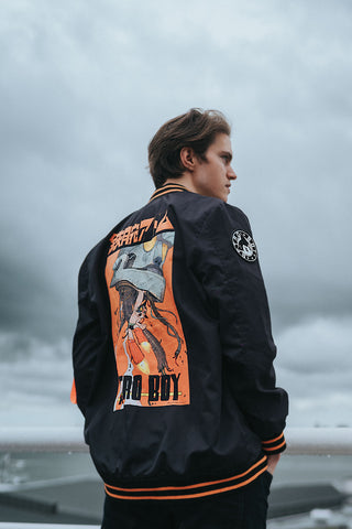 Black Nylon Astroboy Bomber jacket in black and orange. Has a zipper with an orange tag on the left sleeve with Astroboy written on one side and Bibisama on the other. Has Astroboy x Bibisama patch on the right sleeve.
