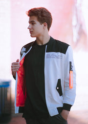 White cotton Astroboy Bomber jacket in white and orange. Has a zipper with an orange tag on the left sleeve with Astroboy written on one side and Bibisama on the other. Has Astroboy x Bibisama patch on the right sleeve. On the left chest, Astroboy is written on top with information on manufacturer and designer.