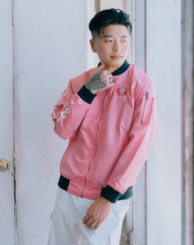 Pink Nylon bomber jacket, influenced by the Chinese Zodiac Pig with zipper on the left sleeve and the pig birth year on the right sleeve.  Has the pig characteristic on the left chest with black and white design inside the jacket. Back of the Jacket is an embroidery of the pig with inside pocket on the left side.