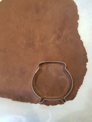 Cutting out the chocolate cookie dough with a cauldron cookie cutter