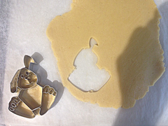 Embossed cookie cutter cutting out cookie dough