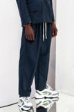 NAVY BLUE TRACKING PANTS with pleats and white jersey drawstring