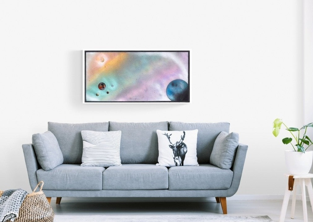 orange, green, purple and blue galaxy abstract painting displayed on a white living room wall