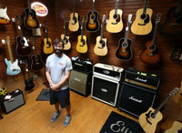 Owner Chris Leitz stands in a room in our store, showcasing top of the line guitars.