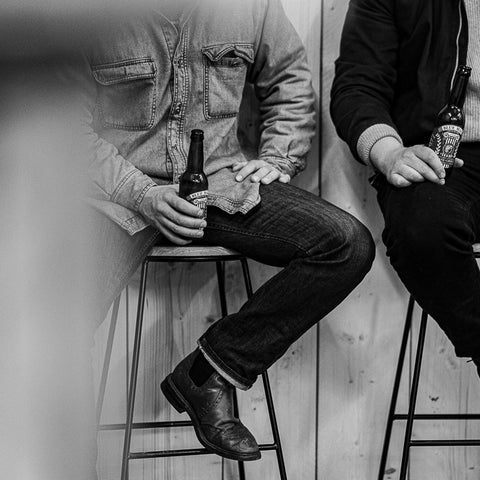 Black and white photo of two men sat on stools enjoying a beer