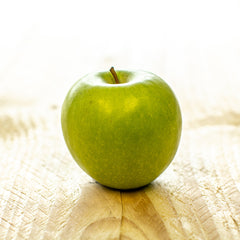 a shiny green apple placed on a wooden board
