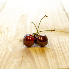 three cherries neatly placed on a wood board