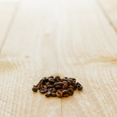 a handful of coffee beans on a wooden board