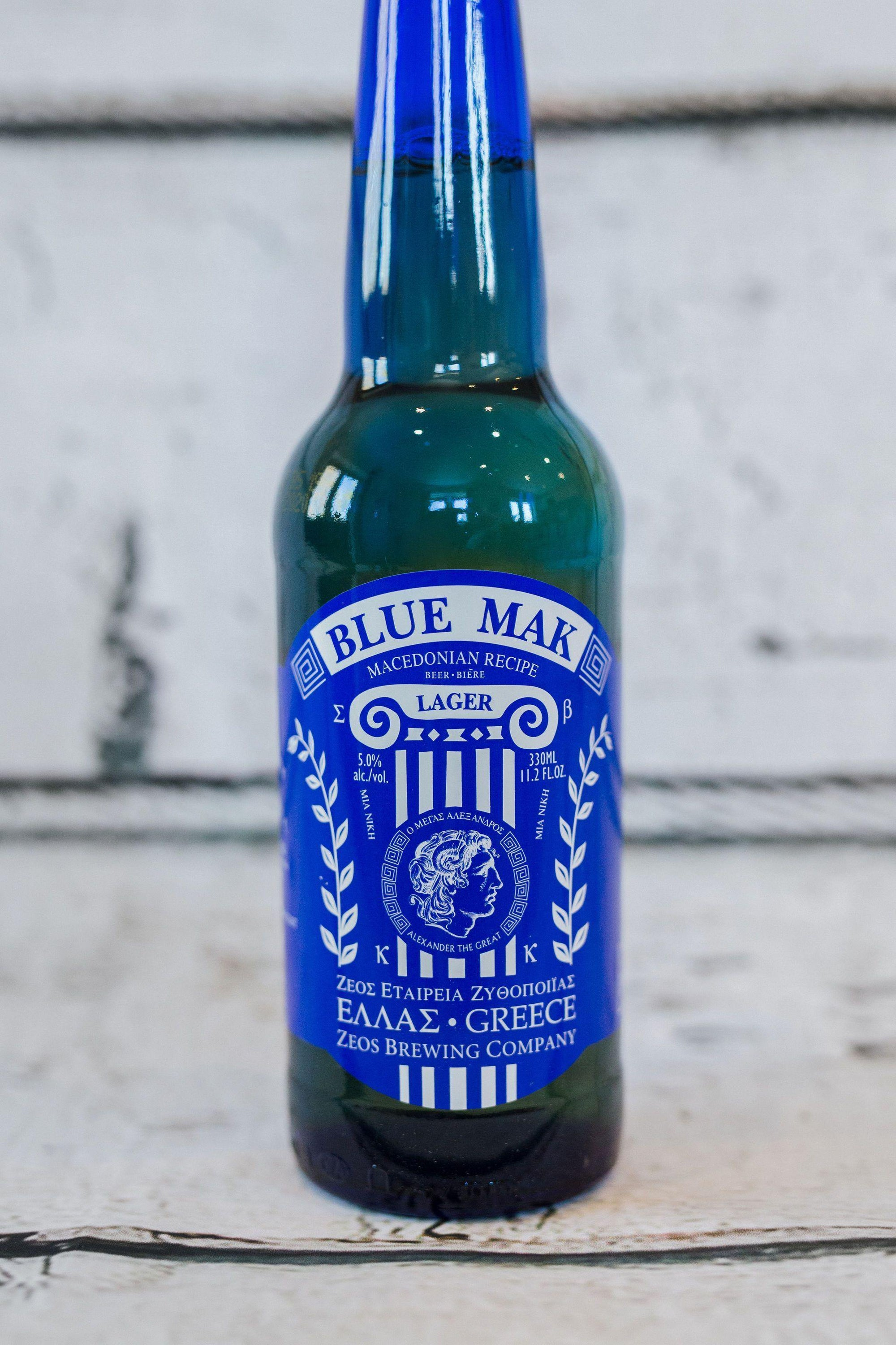 bright blue glass bottle of Blue Mak 330ml Greek beer with Alexander the Great insignia and blue bottle cap
