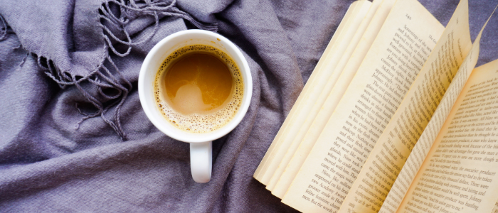book and coffee on bedsheets