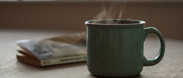 picture of coffee with steam and a book in the background