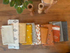 A group of patterned fabrics, ranging from creams to mustards to burnt orange to greys spread out on a walnut table. At the top of the photo is a plant and candlesticks.