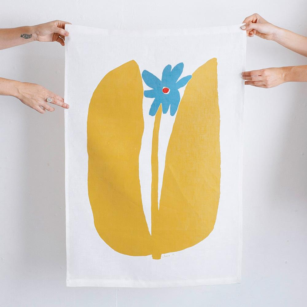 100% Linen Wall Hanging with original design by Claire Ritchie. A large-leafed flower takes up the full canvas. The large yellow leaves dominate the canvas, with a thin yellow stem holding up a blue flower with a red center.