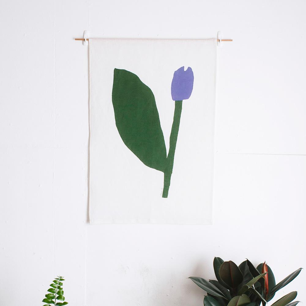 100% Linen Wall Hanging with original design by Claire Ritchie. A large-leafed flower leans to the right of the canvas. The one large dark green leaf dominates the canvas, a sturdy green stem holds up a tulip-like purple flower head.
