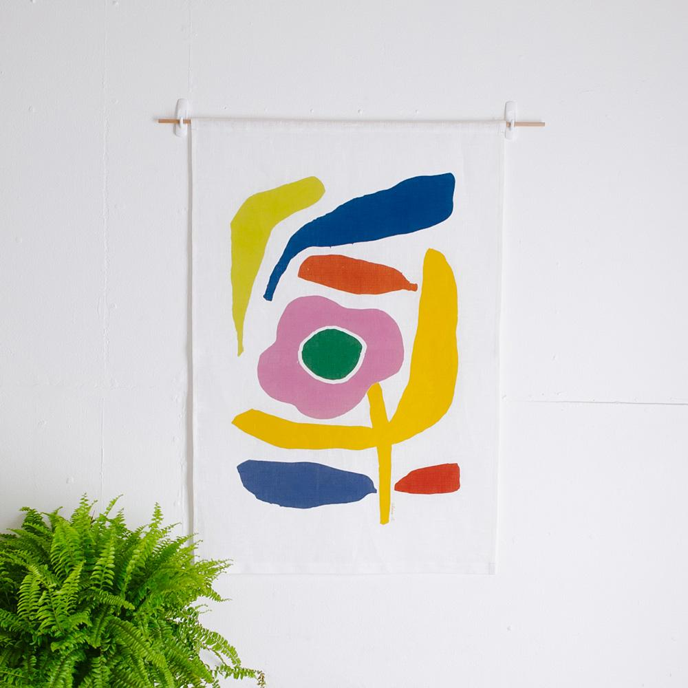 100% Linen Wall Hanging with original design by Claire Ritchie. A dancing multi-coloured flower and abstract shapes fill the canvas. The yellow, pink and green flower sits happily among the abstract shapes.