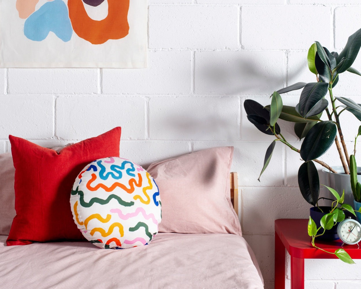 Image shows a circular pillow with thick colorful lines in bright colours. The curving lines appear on a white background in green, dark blue, sky blue, orange, yellow and pink. The Orb Pillow sits on a bed with a red pillow, the Play Wall Hanging sits above it and a plant sits to the right side of the image.