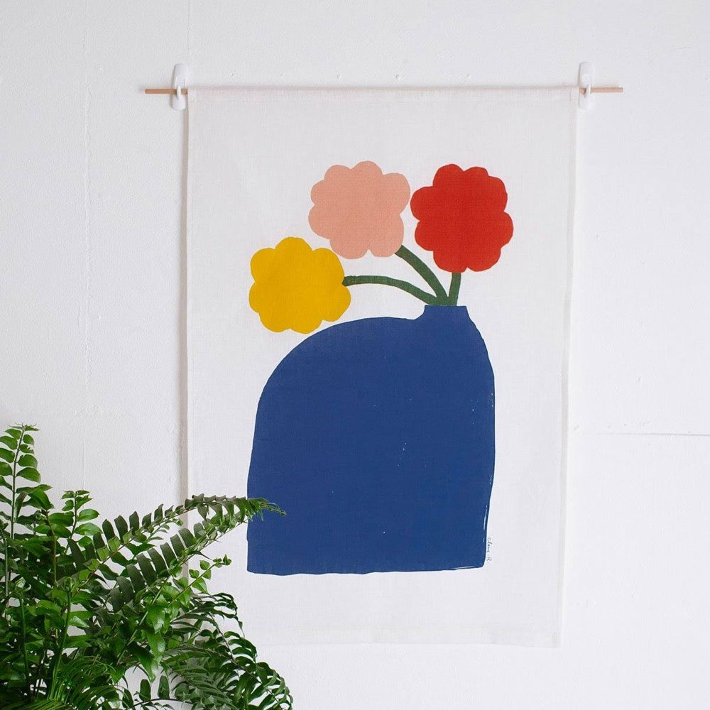 100% Linen Wall Hanging with original design by Claire Ritchie. This wall hanging shows a large blue vase holding three dark green-stemmed flowers with yellow, pink and red blooms. A green house plant sits in the bottom left hand of the picture.