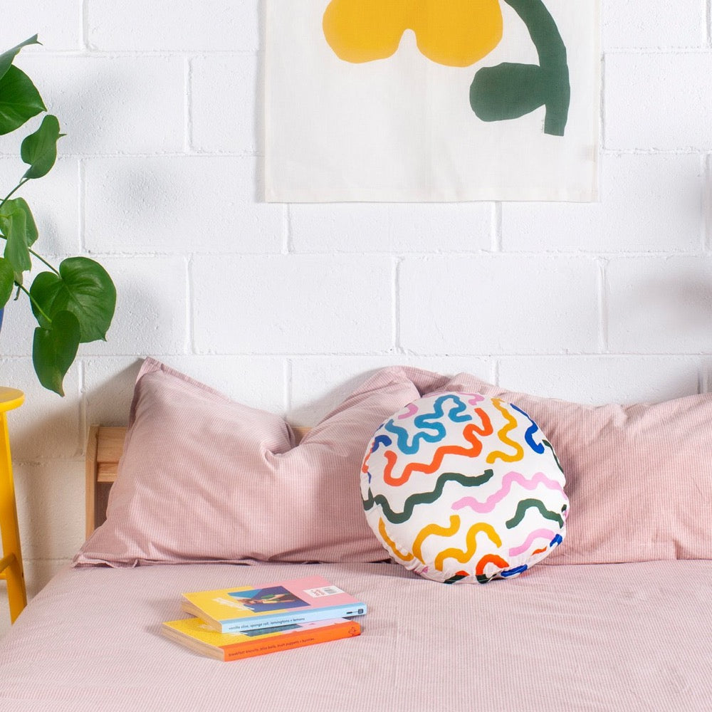 Image shows a circular pillow with thick colorful lines in bright colours. The curving lines appear on a white background in green, dark blue, sky blue, orange, yellow and pink. The Orb Pillow sits on a bed with the Grow Golden Wall Hanging above it.