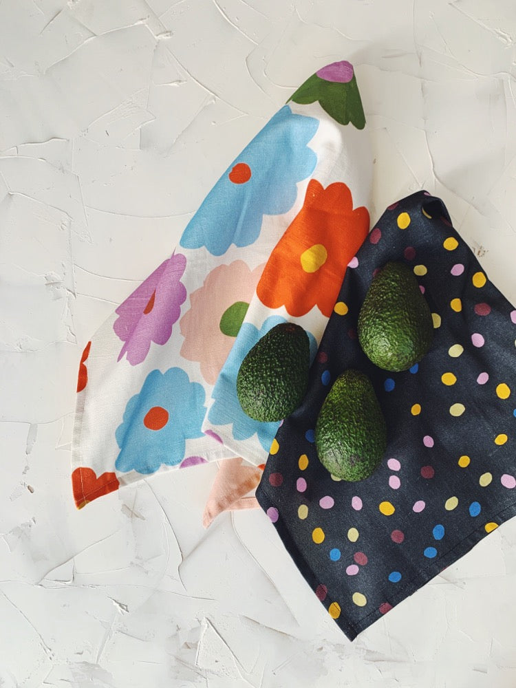 This image shows cotton-linen kitchen towels in the Bloom print (left), and the Spot Speck print (right). Three avocados lay gently on the kitchen towels.