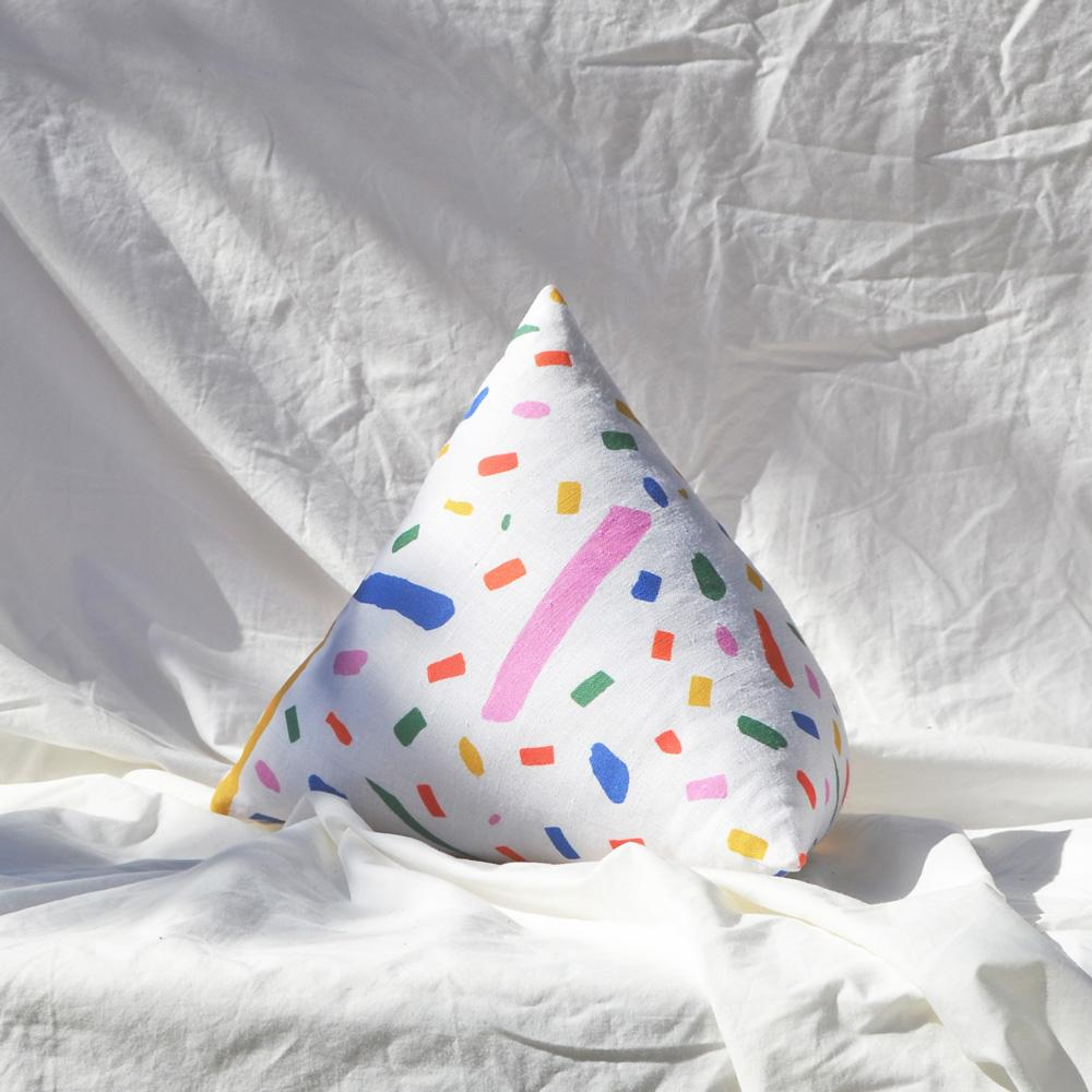 Image shows a pyramid shaped pillow with a patterned exterior. Colourful dashes and dots in pink, blue, green, yellow, red and orange on a white background.
