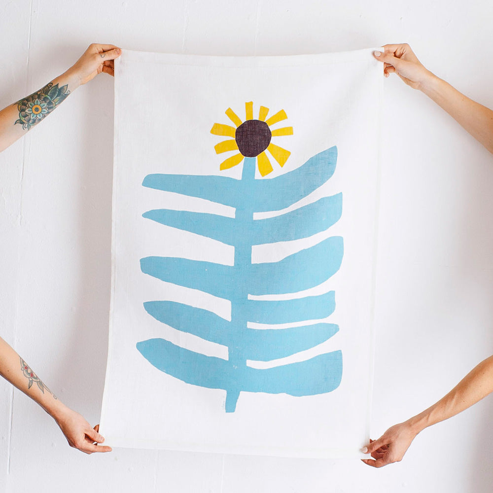 100% Linen Wall Hanging with original design by Claire Ritchie. Two models hold this wall hanging showing a large sunflower with sky blue stem and large horizontal leaves topped with a bright yellow sunflower head with a brown center.