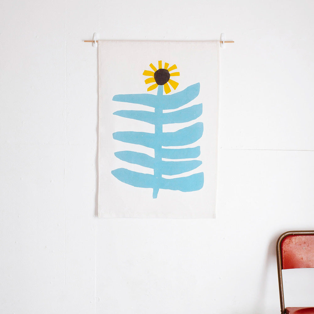 100% Linen Wall Hanging with original design by Claire Ritchie. This wall hanging shows a large sunflower with sky blue stem and large horizontal leaves topped with a bright yellow sunflower head with a brown center. The wall hanging hangs on a white wall with a red chair in the bottom right hand of the image.