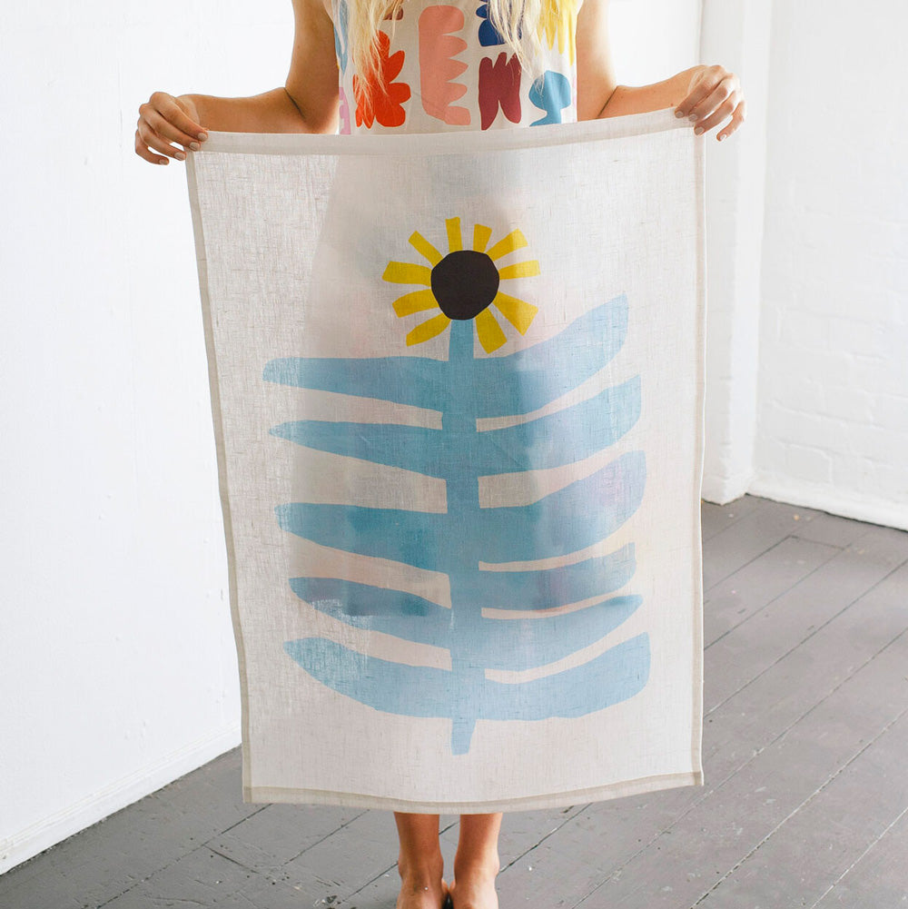 100% Linen Wall Hanging with original design by Claire Ritchie. A model holds this wall hanging showing a large sunflower with sky blue stem and large horizontal leaves topped with a bright yellow sunflower head with a brown center. The image is backlit, showing the texture of the linen hanging in the natural light.