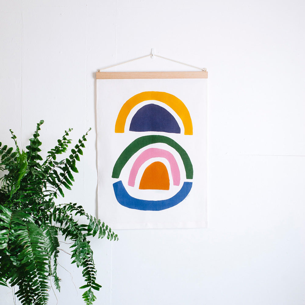 100% Linen Wall Hanging with original design by Claire Ritchie. Multi-coloured, floating arch shapes stacked upon each other. A green house plant sits in the bottom left corner of the image.