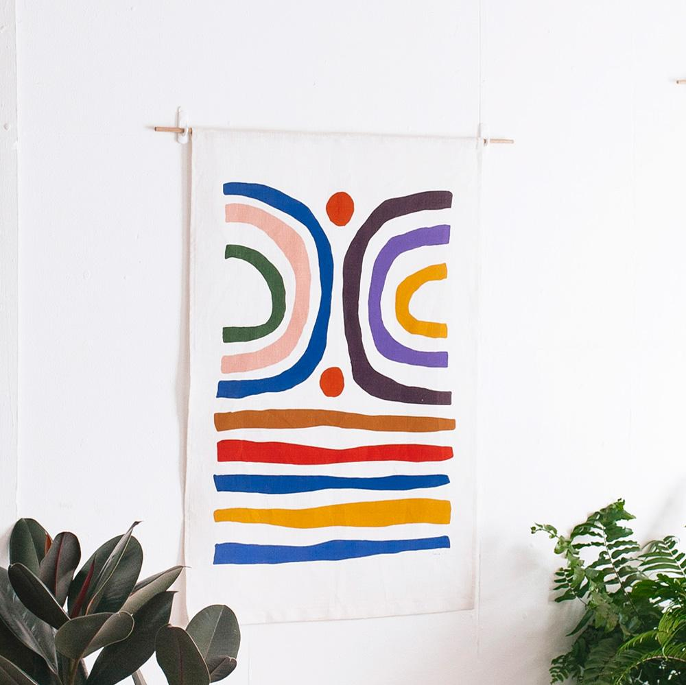 100% Linen Wall Hanging with original design by Claire Ritchie. Two arches sit above horizontal lines in varied colours.