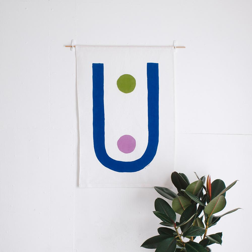 100% Linen Wall Hanging with original design by Claire Ritchie. A large blue u-shape dominates the canvas, holding a purple and a green circle shape within.