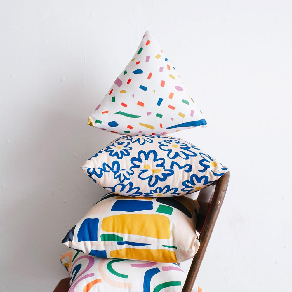 Image shows a pyramid shaped pillow with a patterned exterior stacked on three pillows. The pyramid features colourful dashes and dots in pink, blue, green, yellow, red and orange on a white background.