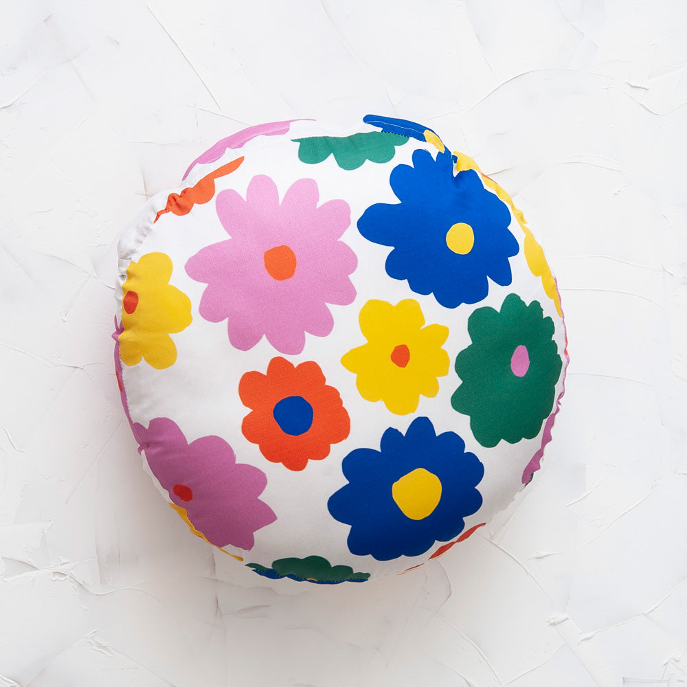 Image shows a circular pillow with a medium to large colorful flower print. The flowers appear on a white background in green, pink, dark blue, red, yellow and pink.