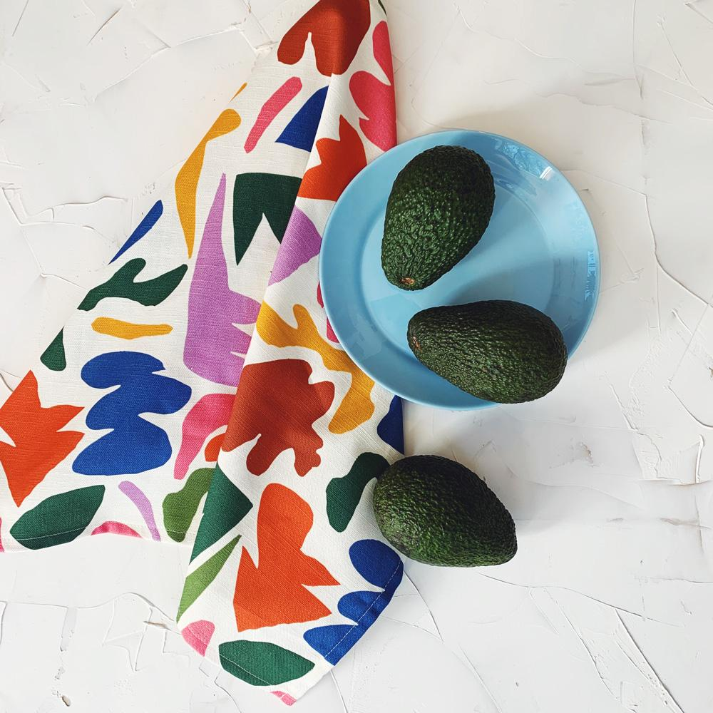This image shows a cotton-linen kitchen towel in the Fracture print, laid beside a blue plate and three market fresh avocados. Small to medium abstract jagged shapes fill the design in saturated bright colours; red, dark red, dark blue, yellow, violet, dark green, olive green and pink.
