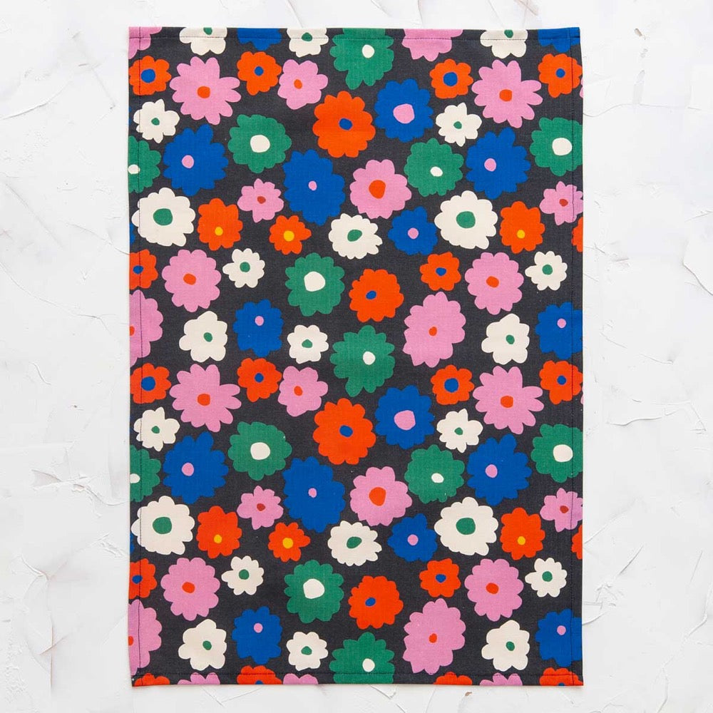 This image shows a cotton-linen kitchen towel in the Power print, laid flat. Small to medium flowers fill the design in saturated bright colours; red, blue, white, green and pink on a black background.